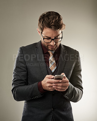 Buy stock photo Studio shot of a handsome young businessman sending a text while standing a grey background
