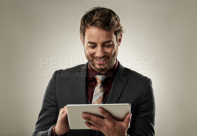 Buy stock photo Studio shot of a handsome young businessman using a digital tablet while standing against a grey background
