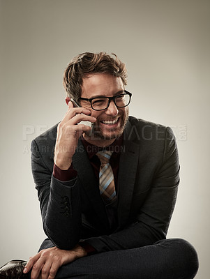 Buy stock photo Studio shot of a handsome young businessman making a call while sitting a grey background