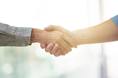 Buy stock photo Cropped shot of two unrecognizable businessmen shaking hands in the office