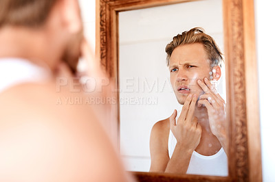 Buy stock photo Shot of a young man examining his skin in the mirror at home
