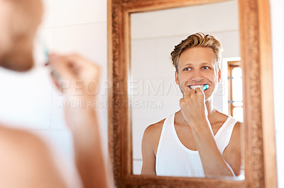 Buy stock photo Shot of a young man brushing his teeth at home
