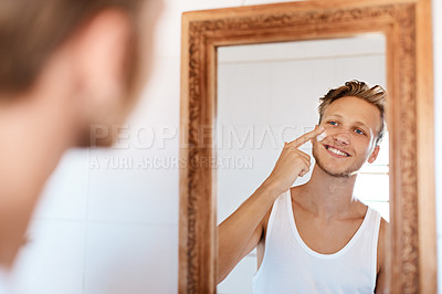 Buy stock photo Shot of a young man applying moisturizer to his face at home