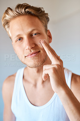 Buy stock photo Portrait of a young man applying moisturizer to his face at home