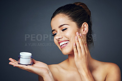 Buy stock photo Studio shot of a beautiful young woman with flawless skin posing with moisturizer against a blue background