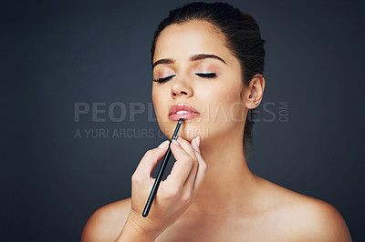 Buy stock photo Studio shot of a beautiful young woman applying lipstick with a lip brush against a blue background