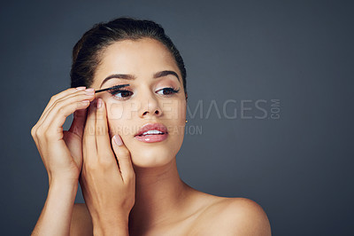 Buy stock photo Studio shot of a beautiful young woman applying mascara while posing against a blue background