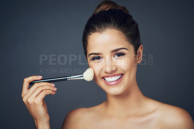 Buy stock photo Studio shot of a beautiful young woman applying blush on her cheeks while posing against a blue background