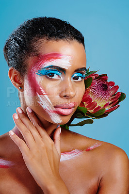 Buy stock photo Studio shot of a beautiful young woman covered in face paint posing against a blue background