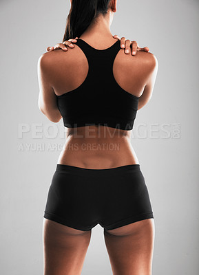 Buy stock photo Rearview shot of a young woman suffering from back pain