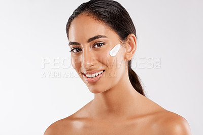 Buy stock photo Studio portrait of a beautiful young woman posing with lotion on her face against a gray background