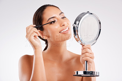 Buy stock photo Studio shot of a beautiful young woman applying mascara using a handheld mirror against a gray background