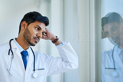 Buy stock photo Shot of a young doctor looking stressed out while standing at a window in a hospital
