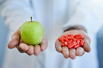 Buy stock photo Closeup shot of an unrecognizable doctor holding an apple and a variety of pills in his hands