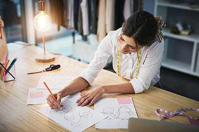Buy stock photo High angle shot of an attractive young fashion designer working on her designs in her workshop