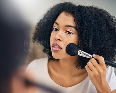 Buy stock photo Shot of a beautiful young woman applying makeup with a brush at home