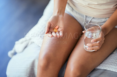 Buy stock photo Cropped shot of a woman taking her medication at home