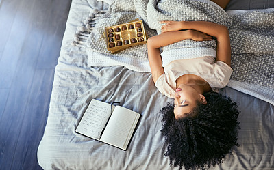 Buy stock photo Shot of a young woman suffering from menstrual cramps in her bedroom