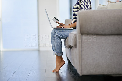 Buy stock photo Cropped shot of a young woman using a laptop and credit card on the sofa at home