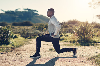 Buy stock photo Full length shot of a handsome young man stretching before exercising outdoors