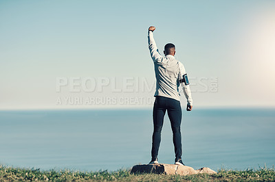 Buy stock photo Rearview shot of an unrecognizable young man standing with his hand raised while exercising outdoors