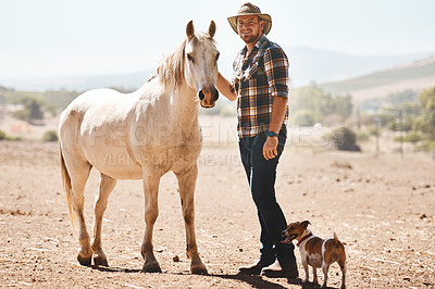 Buy stock photo Portrait of a farmer standing with a horse on a ranch