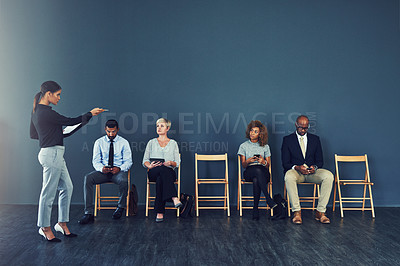 Buy stock photo Shot of a woman pointing at one of the candidates waiting to be interviewed