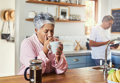 Buy stock photo Shot of a carefree elderly woman sitting at a table in the kitchen drinking coffee and about to sneeze