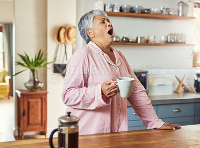 Buy stock photo Shot of a frightful looking elderly woman yelling out in pain and discomfort while drinking coffee in the kitchen