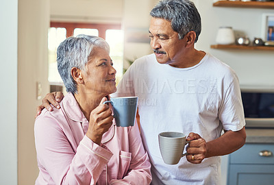 Buy stock photo Shot of a cheerful elderly couple holding each other while looking into each other's eyes and drinking coffee at home during the day