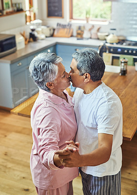 Buy stock photo Shot of a carefree elderly couple having a dance while sharing a kiss inside of the kitchen at home during the day
