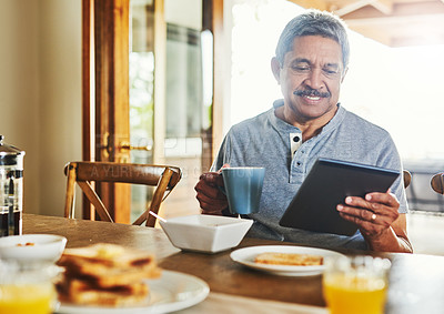 Buy stock photo Shot of a cheerful elderly man browsing on a tablet while having breakfast around  a table at home