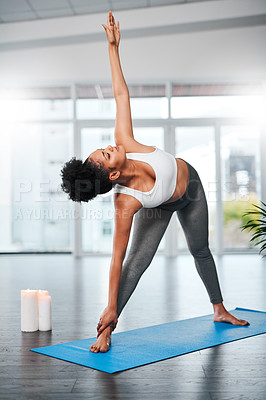 Buy stock photo Shot of a young woman practising yoga in a studio