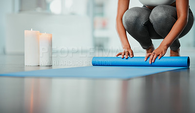 Buy stock photo Cropped shot of an unrecognizable woman rolling up her yoga mat
