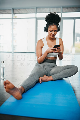 Buy stock photo Shot of a young woman listening to music while doing yoga