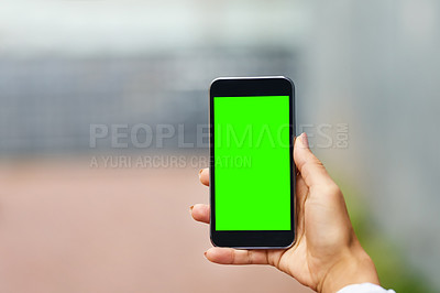 Buy stock photo Closeup shot of an unrecognizable woman holding a cellphone with a green screen screen