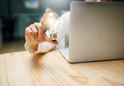 Buy stock photo Closeup shot of an unrecognizable woman holding a lightbulb while using a laptop