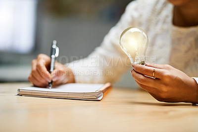 Buy stock photo Closeup shot of an unrecognizable woman holding a lightbulb while writing in a notepad