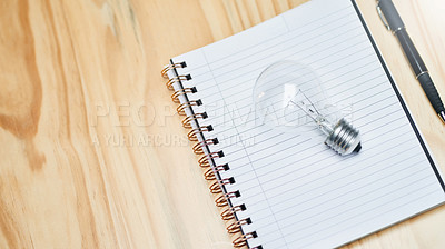 Buy stock photo Still life shot of a lightbulb on a notebook on a table