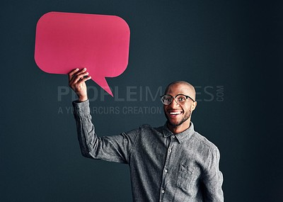Buy stock photo Studio shot of a handsome young man holding a speech bubble