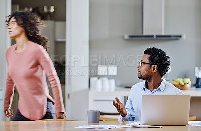 Buy stock photo Cropped shot of a young married couple having a disagreement in the kitchen at home