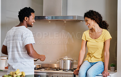 Buy stock photo Cropped shot of a handsome young man cooking while his wife is keeping him company in the kitchen at home