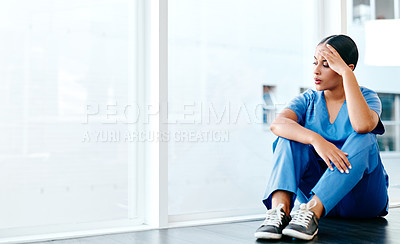 Buy stock photo Shot of a young nurse looking stressed out while sitting at a window in a hospital