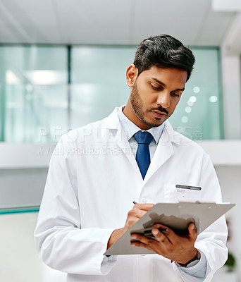 Buy stock photo Shot of a young doctor writing on a clipboard in a hospital