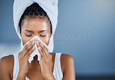 Buy stock photo Shot of an attractive young woman blowing her nose with a tissue at home