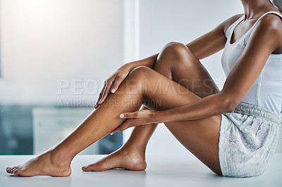 Buy stock photo Cropped shot of a young woman caressing her legs