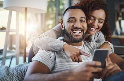 Buy stock photo Cropped portrait of a handsome young man and his girlfriend looking at something on his cellphone while relaxing on the sofa at home