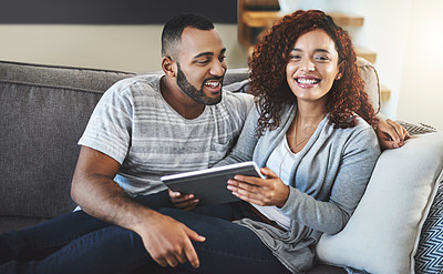 Buy stock photo Cropped shot of an affectionate young couple using their tablet while relaxing on the sofa at home