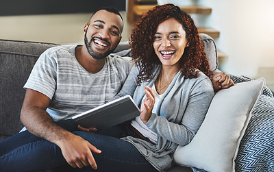 Buy stock photo Cropped portrait of an affectionate young couple using their tablet while relaxing on the sofa at home
