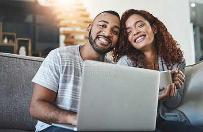 Buy stock photo Cropped portrait of an affectionate young couple using their laptop while relaxing on the sofa at home